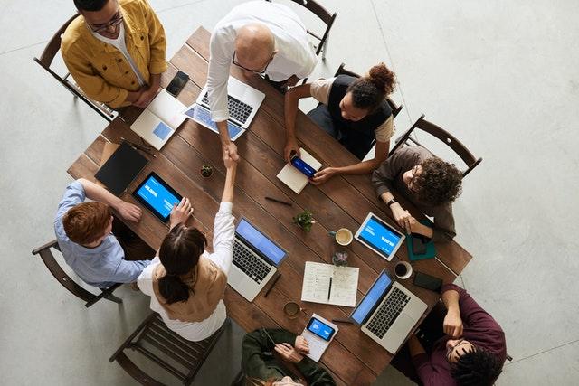 skupina lidí u dřevěného stolu